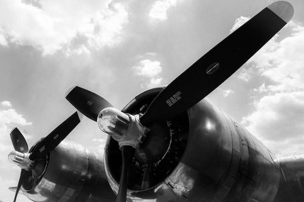 Tiro em escala de cinza de ângulo baixo de duas hélices de um avião pronto para uma decolagem Foto gratuita