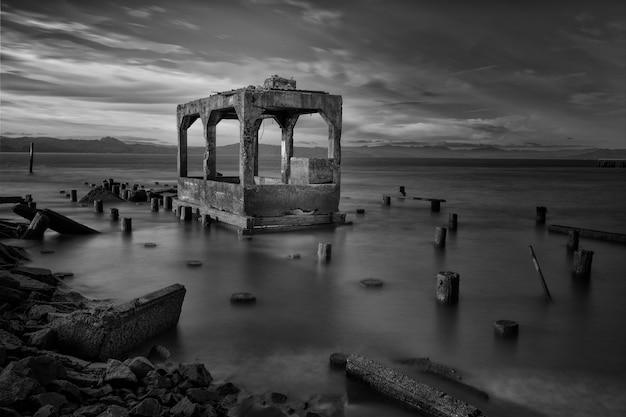 Tiro em escala de cinza de construção de ruínas, rodeado por toras de madeira no mar sob o lindo céu nublado Foto gratuita