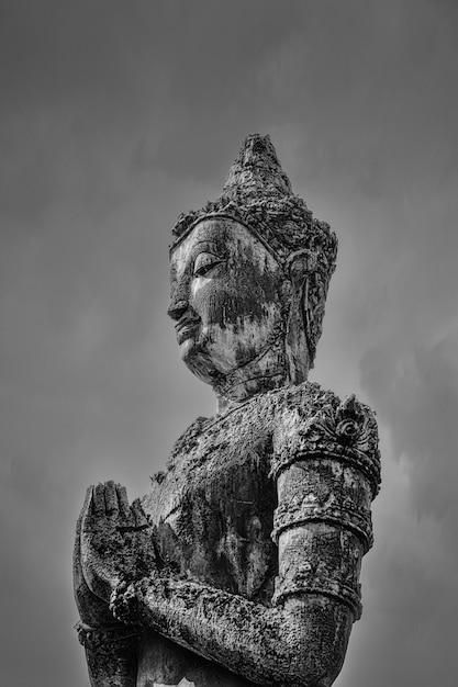Tiro em escala de cinza de uma estátua de buda sob o céu escuro Foto gratuita