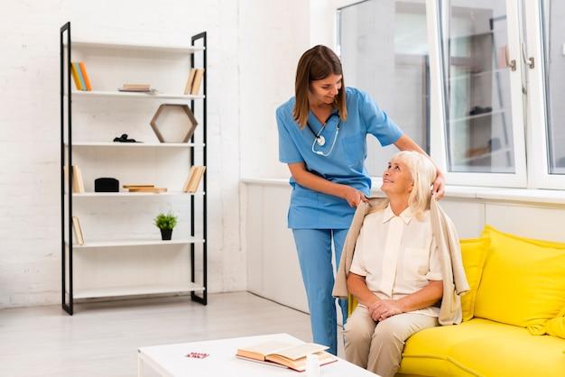 Tiro, enfermeira, ajudando, mulher velha, com, dela, agasalho Foto gratuita