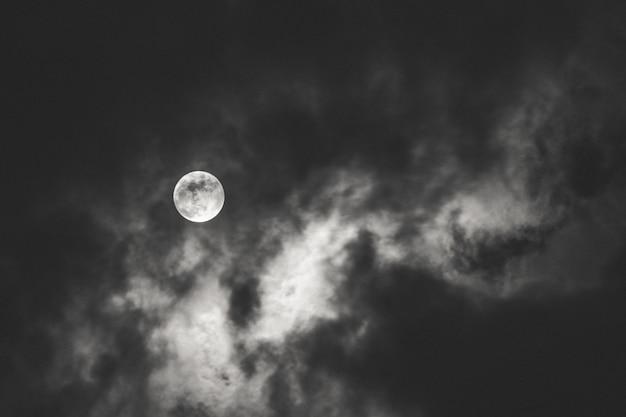 Tiro escuro da lua cheia espalhando luz atrás das nuvens durante a noite Foto gratuita