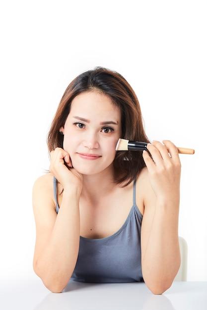 Tiro estúdio, mulher jovem, maquiagem aplicando Foto Premium