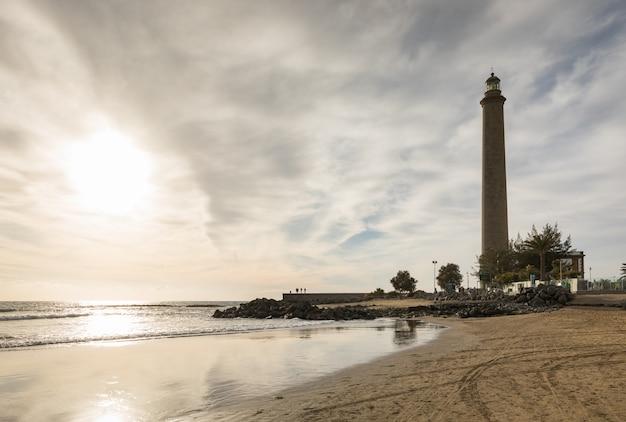 Tiro horizontal da bela praia de maspalomas, com faro de maspalomas ou farol de maspalomas, gran canaria, espanha Foto Premium