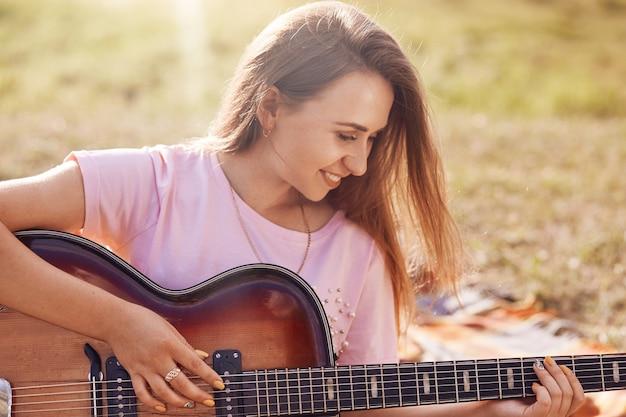 Tiro horizontal da fêmea adorável feliz com sorriso positivo toca guitarra, aprende nova música, recria oudoor no prado, vestido com camiseta casual, tem expressão alegre. pessoas, música, conceito de descanso Foto Premium