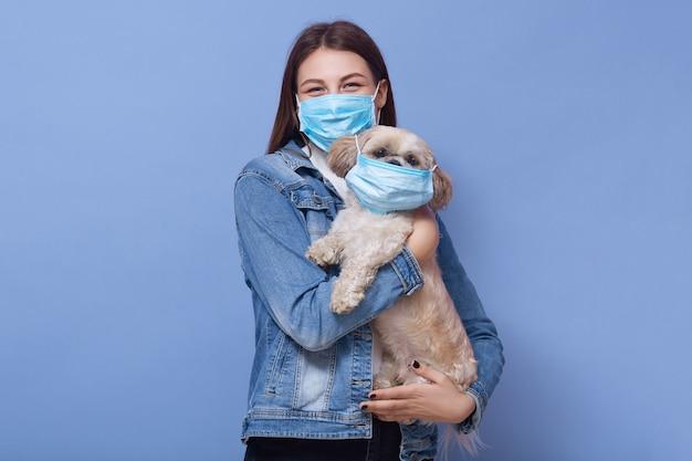 Tiro horizontal da mulher adulta que veste a máscara protetora protegida médica, cão guardando fêmea com máscara também nas mãos, levantando isolado na parede lilás. coronavírus, covid 19, doença, conceito de pandemia. Foto Premium