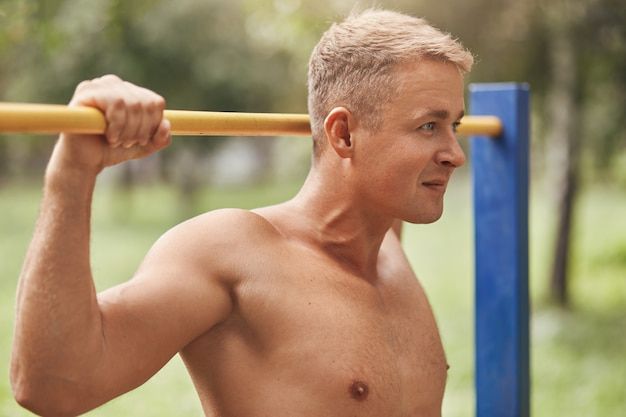 Tiro horizontal de auto-seguro jovem experiente forte desportista tem músculos Foto gratuita