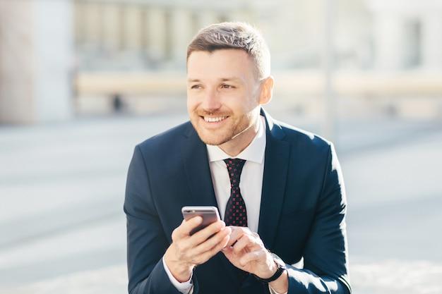 Tiro horizontal de homem atraente com expressão pensativa alegre, usa telefone celular moderno Foto Premium