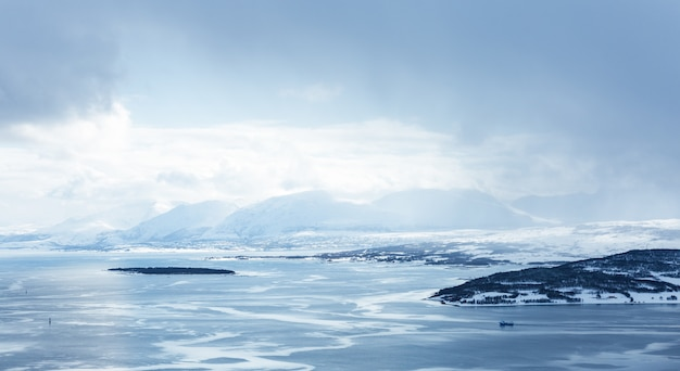 Tiro horizontal de um corpo de água coberto de gelo, rodeado por montanhas sob as nuvens brancas Foto gratuita