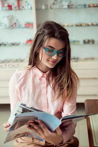 Tiro horizontal do cliente feminino caucasiano bonito sentado em copos prescritos na moda, lendo revista e sorrindo, esperando na fila para oftalmologista para check-up regular Foto gratuita