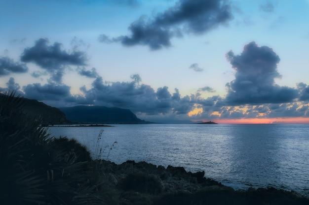 Tiro horizontal do mar calmo sob o céu nublado louco à noite Foto gratuita