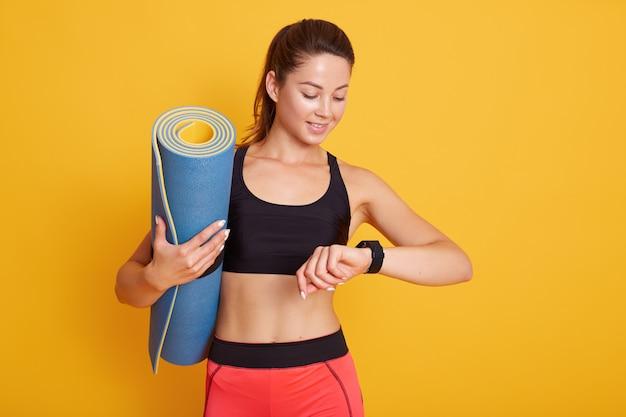 Tiro horozontal de mulher fitness após a sessão de treino verifica os resultados no smartwatch no aplicativo de fitness, fêmea com corpo perfeito isolado sobre fundo amarelo. estilo de vida saudável e conceito de esporte. Foto Premium
