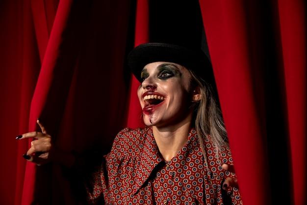 Tiro intenso de uma mulher de maquiagem de halloween rindo Foto gratuita