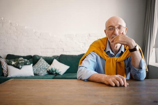 Tiro interno de bonito homem maduro idoso com olhos sábios, sentado na mesa de madeira com sofá com expressão pensativa, tocando o rosto. pessoas, estilo de vida e idade Foto gratuita