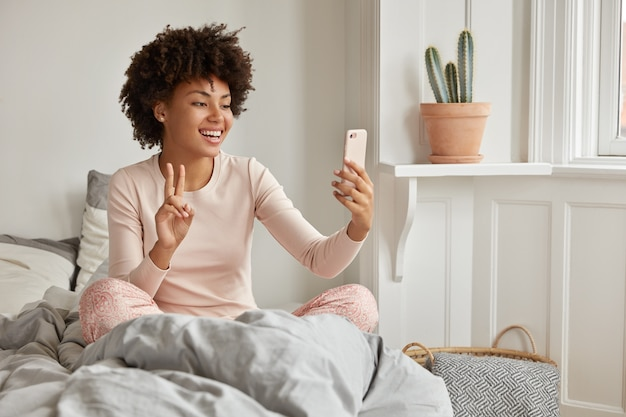 Tiro interno de mulher alegre de pele escura vestida com pijama casual, tem videochamada matinal, segura o telefone celular moderno, posa na cama, sorri amplamente, mostra o símbolo da paz na tela. selfie de manhã Foto gratuita