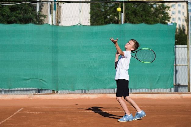 Tiro longo, criança, servindo, ligado, tênis, campo Foto gratuita