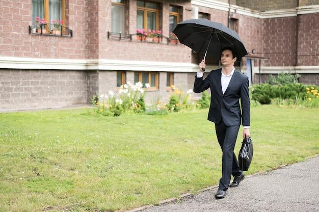 Tiro longo, de, homem negócios, segurando guarda-chuva Foto gratuita
