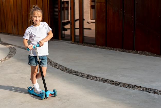 Tiro longo, de, menina, montando, azul, scooter Foto gratuita