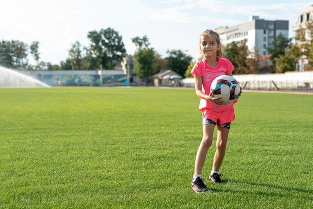 Tiro longo, de, menina, segurando, um, bola Foto gratuita