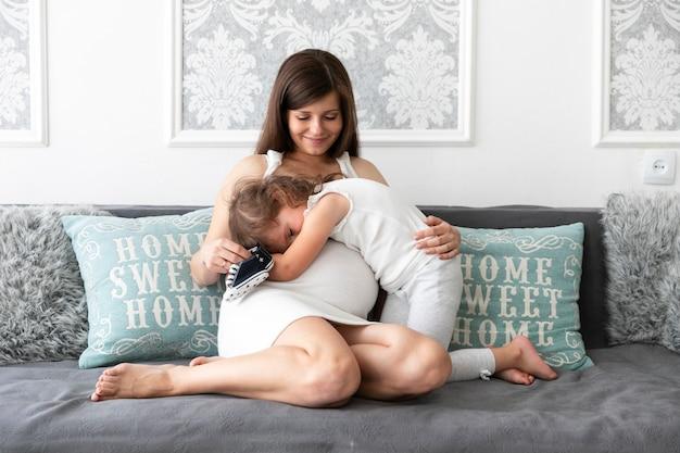 Tiro longo, filha, abraçando, dela, mãe, sofá Foto gratuita