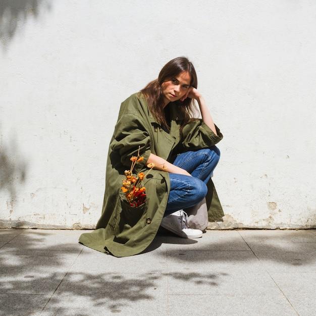 Tiro longo, moda, mulher, agachando-se Foto gratuita