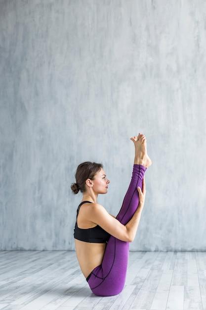Tiro longo, mulher, sentando, em, um, posição ioga Foto gratuita