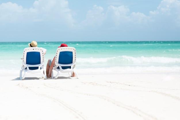 Tiro longo, vista traseira, de, par, sentando, ligado, cadeiras praia Foto gratuita