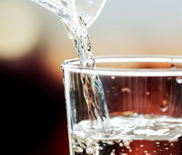 Tiro macro de derramar água em um copo Foto gratuita