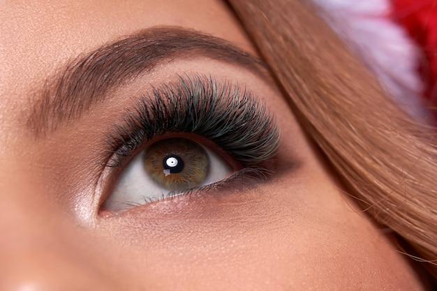 Tiro macro linda de olhos femininos com cílios longos extremos e maquiagem delineador preto Foto Premium