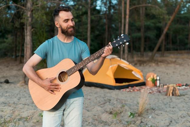 Tiro médio, acampamento, homem, violão jogo Foto gratuita