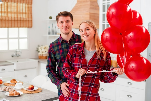 Tiro médio casal feliz com balões Foto gratuita