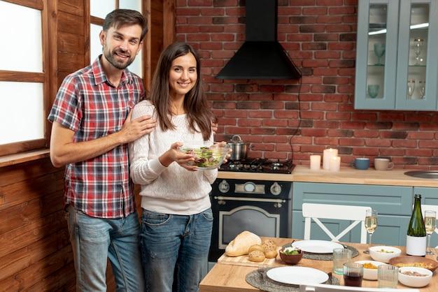 Tiro médio casal feliz com uma tigela de comida Foto gratuita