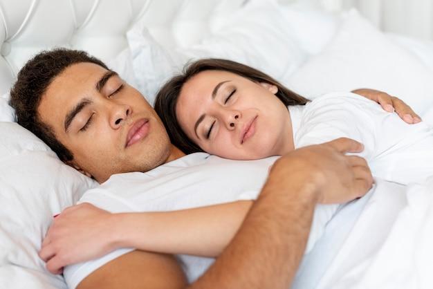 Tiro médio casal feliz dormindo juntos Foto gratuita