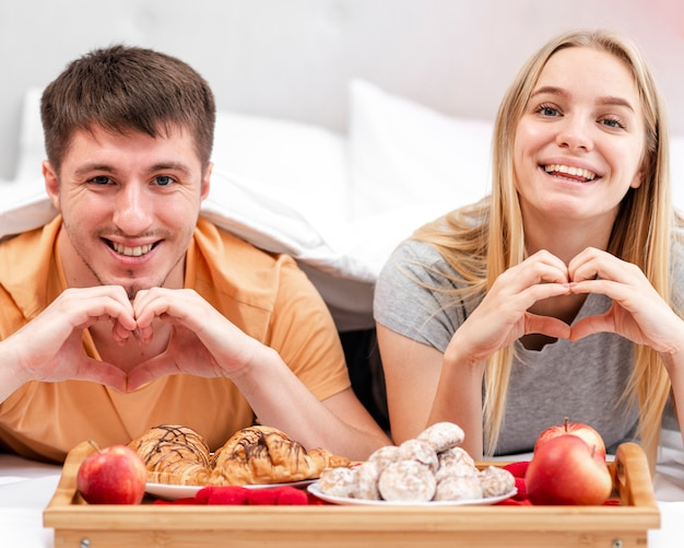 Tiro médio casal feliz em forma de coração gesto com a mão Foto gratuita