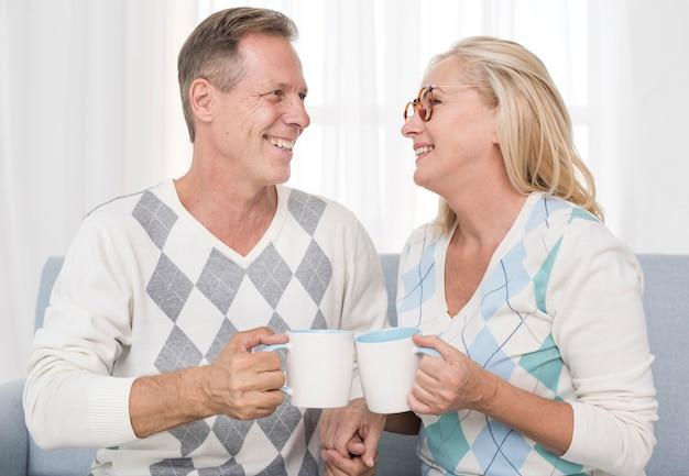 Tiro médio casal feliz segurando canecas brancas Foto gratuita