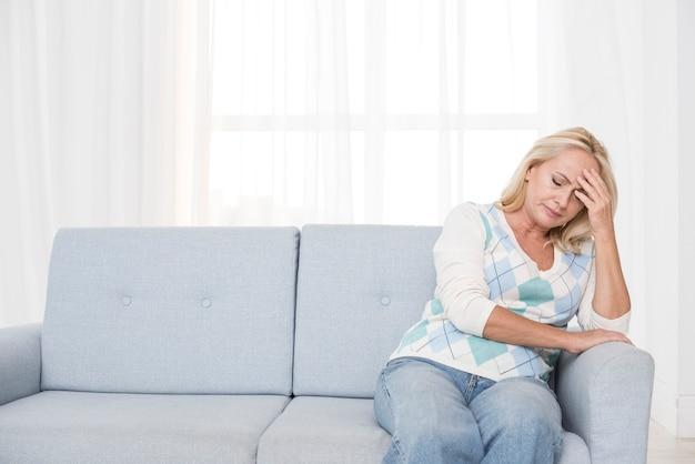 Tiro médio chateado mulher sentada no sofá Foto gratuita