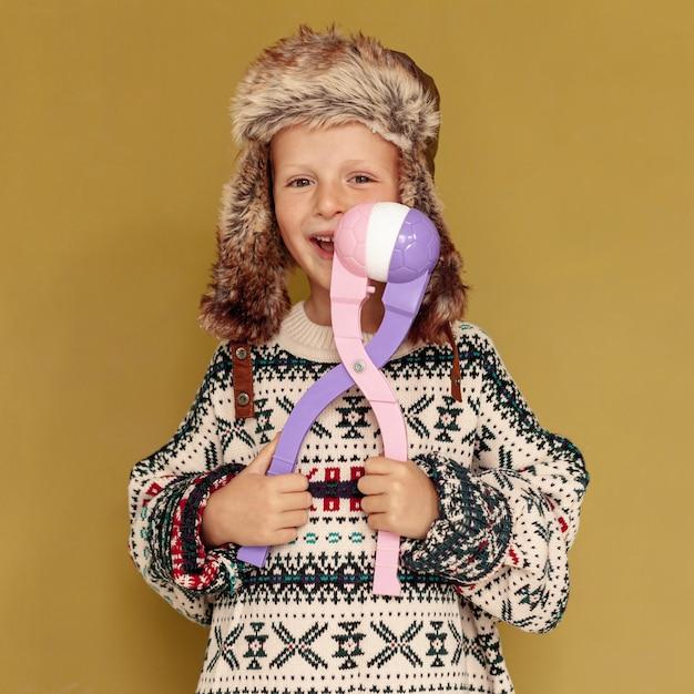 Tiro médio criança feliz com brinquedo e chapéu Foto gratuita