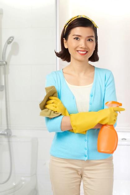 Tiro médio da jovem governanta asiática posando durante a limpeza do banheiro Foto gratuita