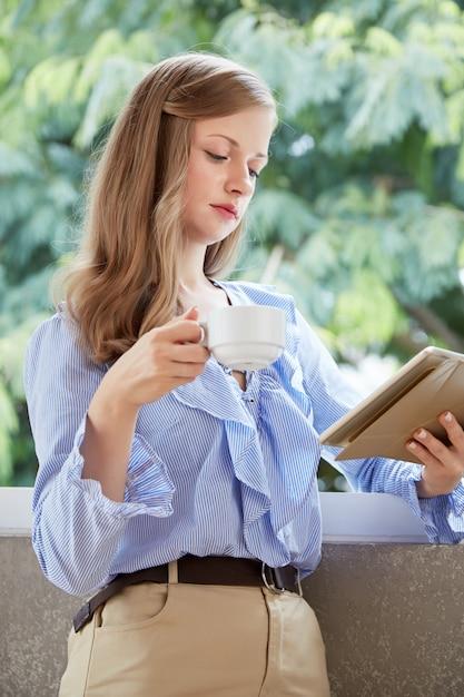 Tiro médio da jovem mulher loira em pé na varanda com uma xícara de café e tablet pc lendo Foto gratuita
