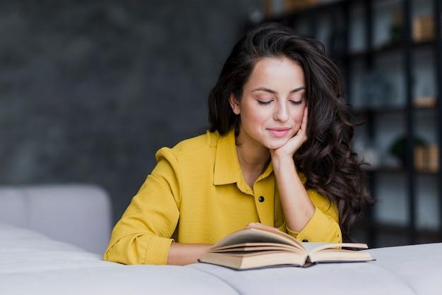Tiro médio da mulher do smiley que lê Foto gratuita