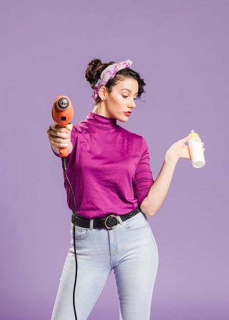 Tiro médio da mulher prática segurando broca e mamadeira vista frontal Foto gratuita
