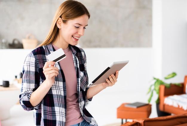 Tiro médio da mulher segurando seu cartão de crédito e olhando para o tablet Foto gratuita