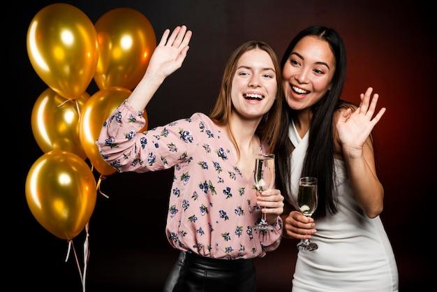 Tiro médio das mulheres na festa posando com champanhe Foto gratuita