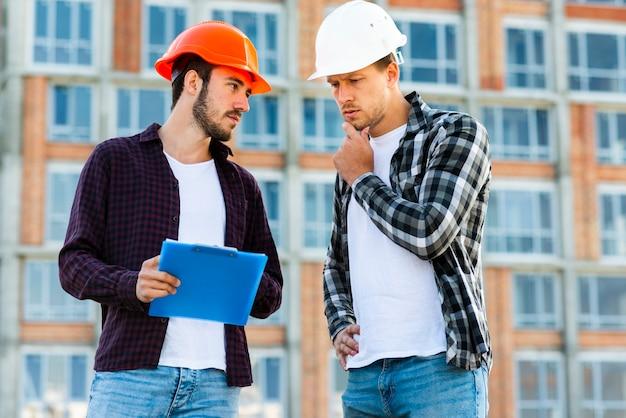 Tiro médio, de, engenheiro, e, trabalhador construção, falando Foto gratuita