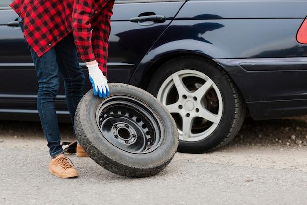 Tiro médio, de, homem, com, sobressalente, pneu Foto gratuita