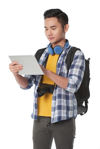 Tiro médio de jovem com mochila usando o tablet pc Foto gratuita