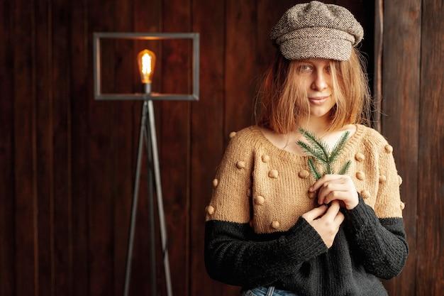 Tiro médio de menina bonita com galho de árvore do abeto e lâmpada Foto gratuita