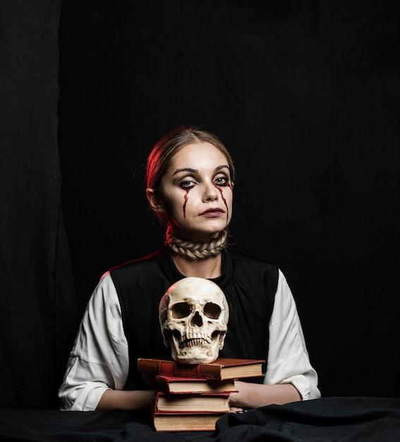 Tiro médio, de, mulher, com, livros, e, cranio Foto gratuita