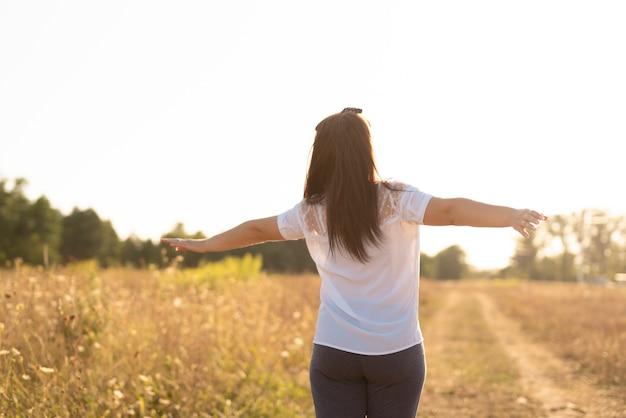 Tiro médio de uma jovem mulher segurando os braços no ar Foto gratuita