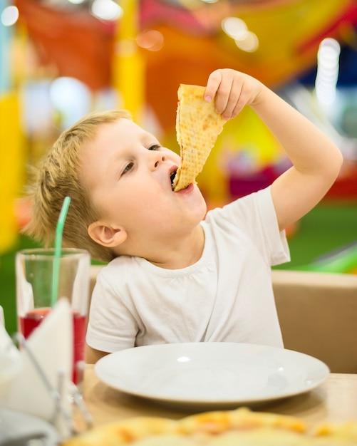 Tiro médio do garoto comendo pizza Foto gratuita