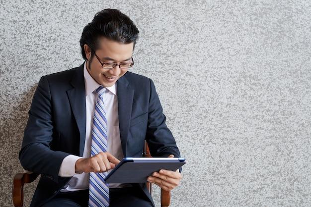 Tiro médio do homem de negócios asiáticos usando o teclado digital Foto gratuita